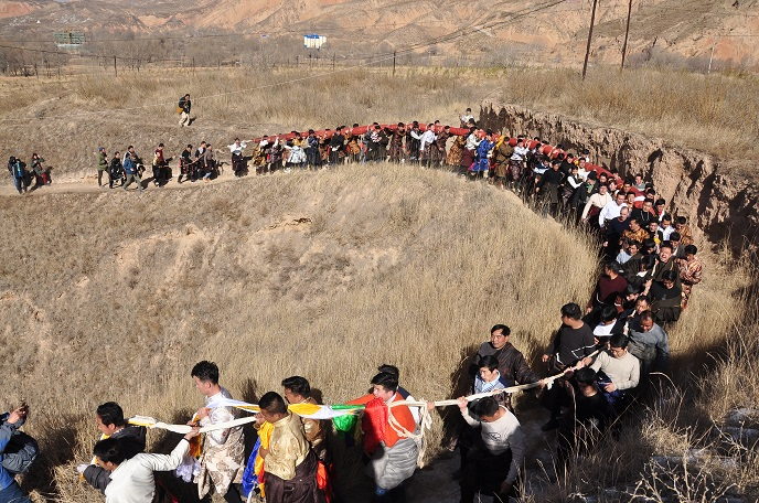 Monks and Believers Are Carrying A Roll of Huge Thangka to the Hillside