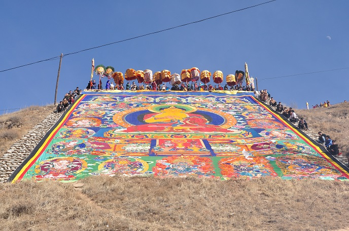 A Giant Thangka is Being Displayed along the Hillside